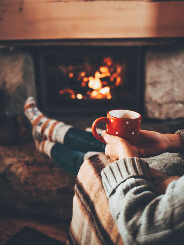 Person Holding Mug, Lounging by Fireplace